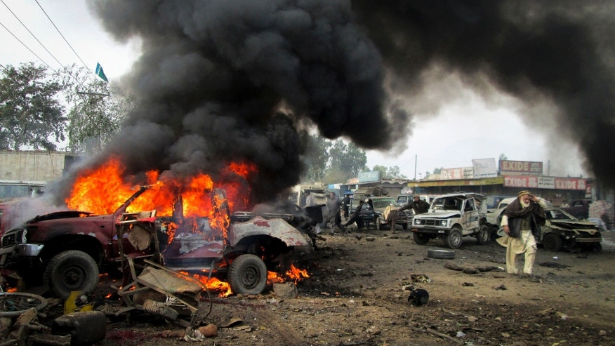 Dec. 17, 2012 - A Pakistani man walks past a burning vehicle after a blast in the Pakistani tribal area of Khyber.