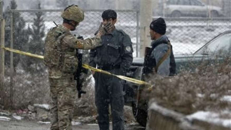 December 17, 2012: Afghan policemen and a NATO soldier talk as they stand guard at the site of an explosion in Kabul .