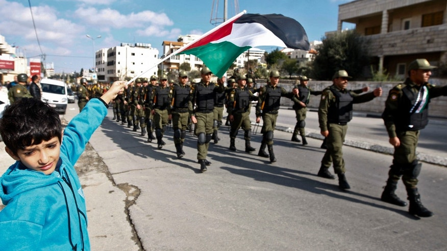 Dec. 17, 2012 - A Palestinian youth waves a flag as security officers march in support of Palestinian President Mahmoud Abbas, and to celebrate their successful bid to win U.N. statehood recognition the in the West bank city of Bethlehem.