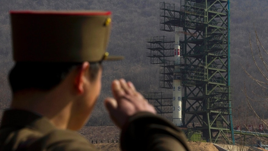 April 8, 2012: In this file photo, a North Korean soldier salutes in front of the country's Unha-3 rocket at Sohae Satellite Station in Tongchang-ri, North Korea.