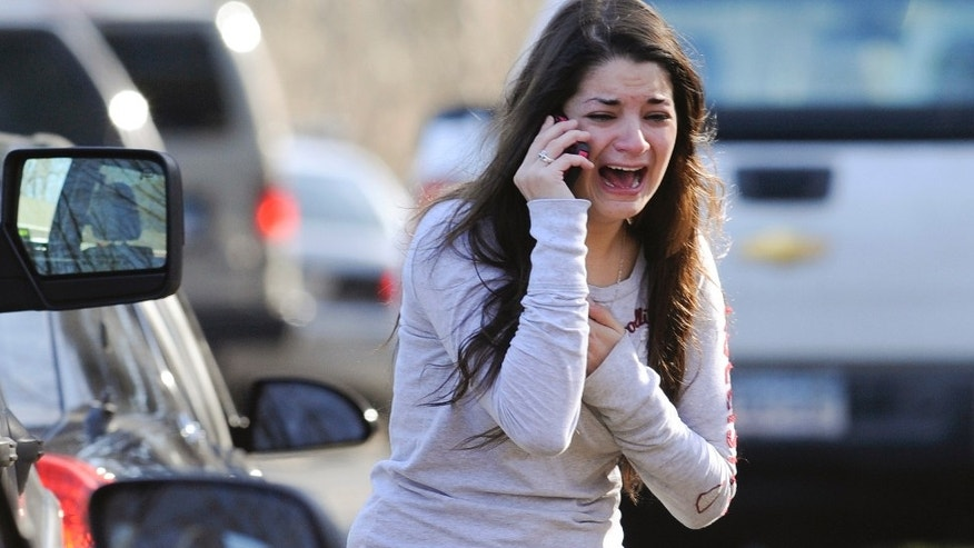 Carlee Soto uses a phone to get information about her sister, Victoria Soto, a teacher at the Sandy Hook elementary school in Newtown, Conn. Friday, Dec. 14, 2012 after a gunman killed over two dozen people, including 20 children. Victoria Soto, 27, was among those killed. (AP Photo/Jessica Hill)