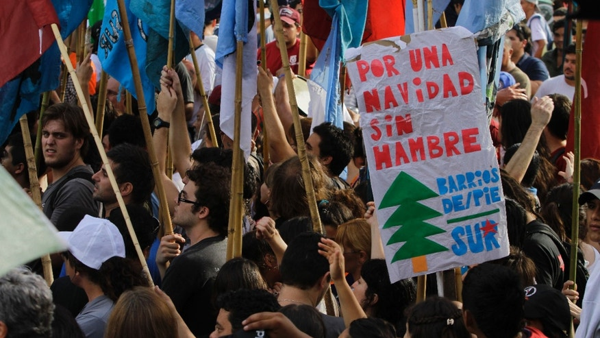 "People demonstrate during a protest in Plaza de Mayo main square in Buenos Aires, Argentina, Wednesday, Dec. 19, 2012. Thousands of people crowded the square in front of the presidential palace to demand salary hikes and a solution to spiraling inflation. The sign reads in Spanish ""for a Christmas without hungry.""  (AP Photo/Eduardo Di Baia)"