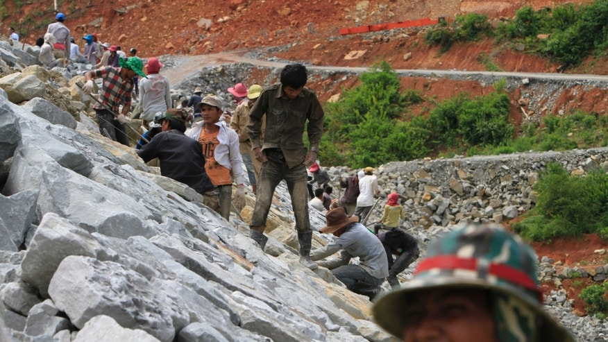 In this Oct. 6, 2012 photo, local workers adjust stones at a dam construction site by China National Heavy Machinery Corporation on the Tatay River in Koh Kong province, some 210 kilometers (130 miles) west of Phnom Penh, Cambodia. Up a sweeping, jungle valley in a remote corner of Cambodia, Chinese engineers and workers are raising a 100-meter-(330-foot-) high dam over the protests of villagers and activists. Only Chinese companies are willing to tame the Tatay and other rivers of Koh Kong province, one of Southeast Asia's last great wilderness areas. (AP Photo/Heng Sinith)