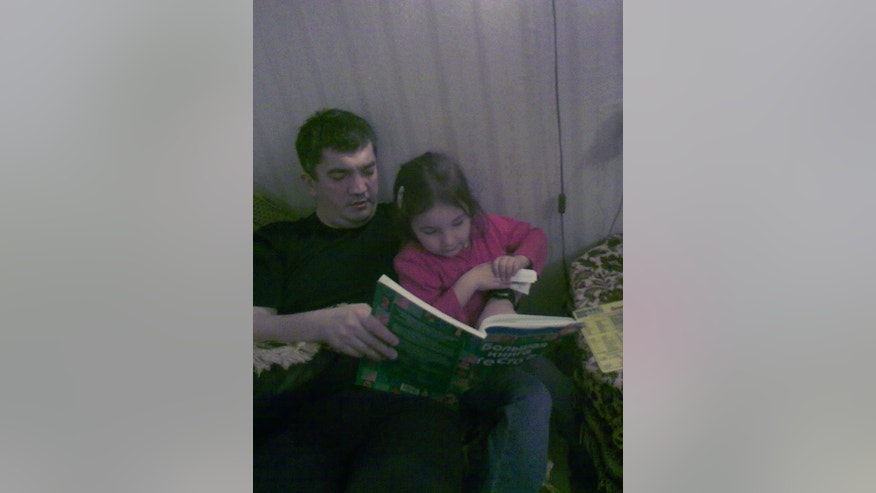 In this undated Gunahev family handout photo made avaliable on Thursday, Dec. 6, 2012, anesthesiologist Marat Gunashev reads a book for his daughter at his home in Makhachkala, a provincial capital of Dagestan, Southern Russia. The anesthesiologist was performing surgery in this hospital, when armed police burst into the hospital and arrested him, still wearing his medical clothes, leaving the patient lying unconscious on the operating table. Now Marat Gunashev faces charges of organizing an attack by Islamic militants three years ago that killed the police chief in Makhachkala, a provincial capital in Russia's restive Caucasus.  (AP Photo/Gunashev Family)
