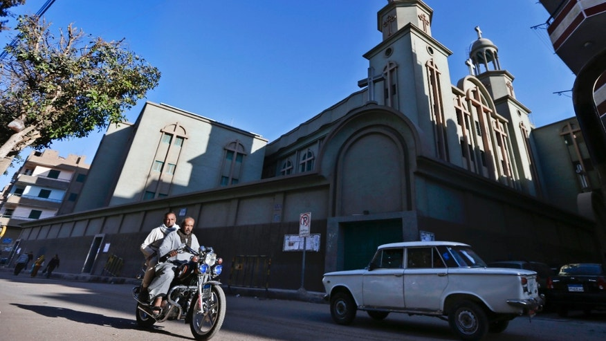 Dec. 18, 2012: Men ride a motorcycle past a church in Assiut, southern Egypt.