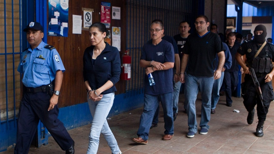 "Escorted by police officers, alleged members of an organized crime group, among them the Mexican citizen Raquel Alatorre Correa, second from left, arrive to a court to attend their trial in Managua, Nicaragua, Wednesday, Dec. 19, 2012. Correa and other alleged members of the group, who are facing charges of organized crime and money laundering, were detained on Aug. 24 in Las Manos, Nicaragua, while they were traveling inside a Televisa TV truck with ""press badges,"" high–definition video cameras, microphones and a satellite dish, and ,according to authorities, hidden beneath the sound boards and screens in three of the vans, police officers found black gym bags stuffed with $9.2 million in cash for alleged use in drug trafficking. (AP Photo/Esteban Felix)"