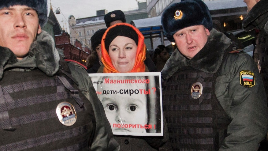 Dec. 19, 2012: Police officers detain a protester near the State Duma, in Moscow, Russia. People picket parliament's lower chamber, to protest against planned debate of an amendment that would ban Americans from adopting Russian children. The poster reads: Are orphans guilty of Magnitsky's death ? Stop putting shame on yourselves!