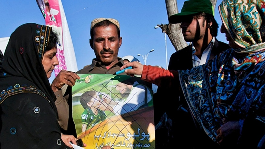 Dec. 19, 2012: Pakistani polio workers cross out an anti-polio campaign poster during a demonstration against the killing of their colleagues, in Islamabad, Pakistan.