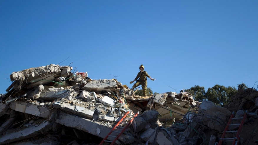 An Israeli military officer from the Home Front command rescue unit stands on the ruins of a school during a Home Front command drill, simulating a rocket barrages hitting the country's cities, in Holon, near Tel Aviv, Israel, Tuesday, Dec. 18, 2012. (AP Photo/Ariel Schalit)