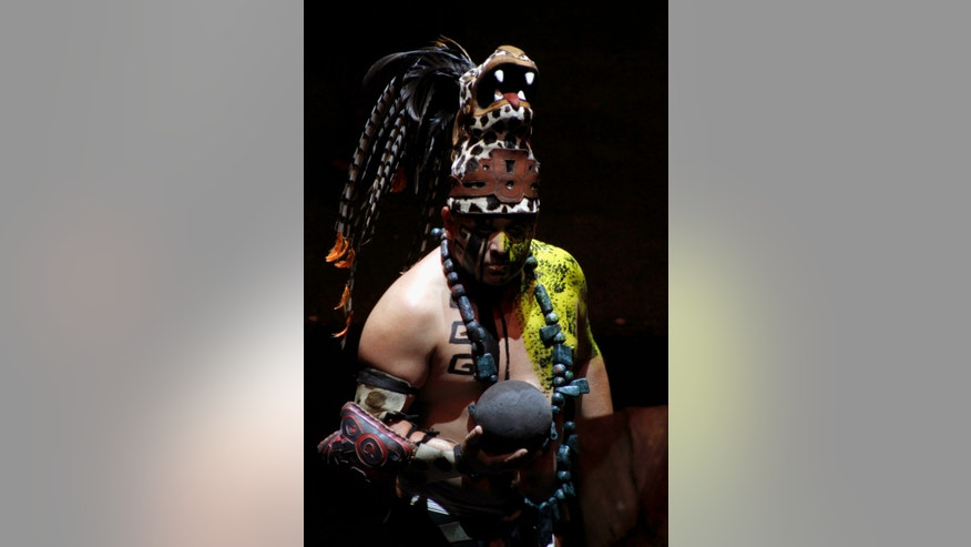 A Mayan dancer performs at the Xcaret Eco Theme Park on the outskirts of Playa del Carmen, Mexico, Wednesday, Dec. 19, 2012. Amid a worldwide frenzy of advertisers and new-agers preparing for a Maya apocalypse, one group is approaching Dec. 21 with calm and equanimity, the people whose ancestors supposedly made the prediction in the first place. (AP Photo/Israel Leal)
