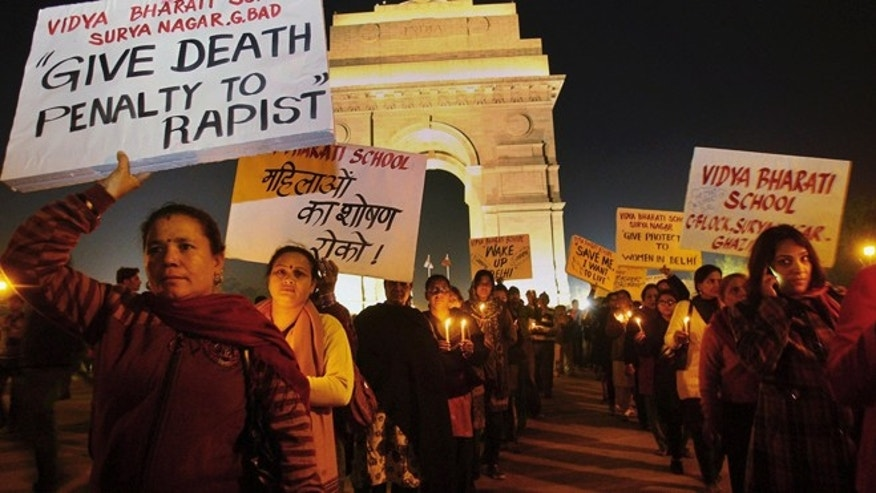 Dec. 20, 2012: Indian people hold placards as they participate in a candlelight vigil at India Gate in New Delhi, India for a woman raped on a bus.