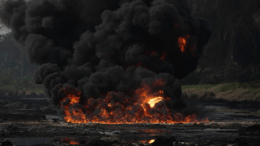 Smoke and flames billow from a burning oil pipeline in Ijeododo on the outskirts of  Lagos, Nigeria  Thursday, Dec. 20, 2012. The oil pipeline belonging to Nigeria National Petroleum Cooperation exploded near Nigeria's largest city as thieves tried to siphon oil from it Monday. (AP Photo/Sunday Alamba)