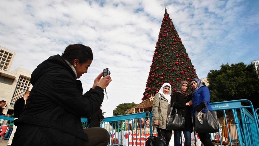 Dec. 17, 2012 - Palestinian Muslim women pose for a photo near a Christmas tree in Manger Square, outside the Church of the Nativity, in Bethlehem.