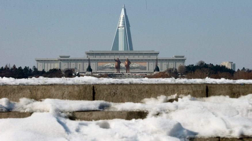 Dec. 17, 2012 - North Koreans pay their respects before the statues of late leaders Kim Il Sung, left, and Kim Jong Il, right, at Mansu Hill near the pyramid shaped 105-story Ryugyong Hotel in Pyongyang, North Korea.