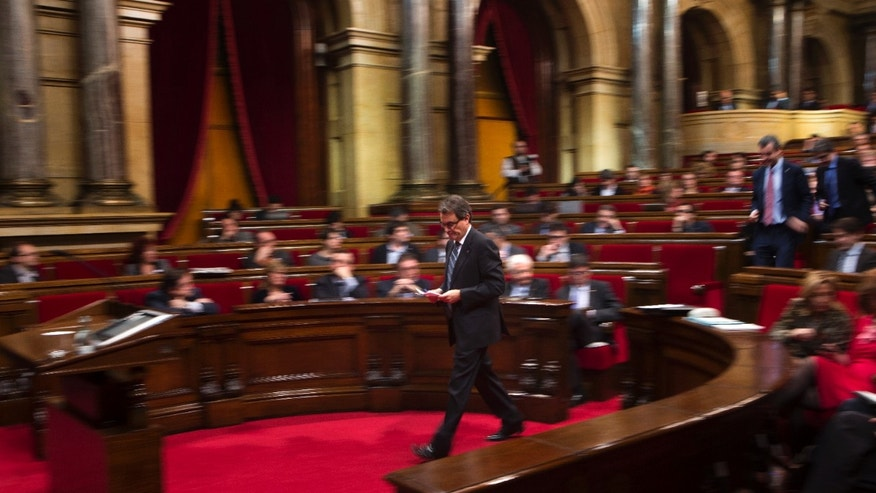 Artur Mas, head of the Convergence and Union, walks to the stand to deliver a speech at the parliament in Barcelona, Spain, Friday Dec. 21, 2012. Regional parliament deputies in Catalonia have voted back into office a president who has promised to stage a hugely controversial referendum on independence from Spain. Artur Mas, head of the Convergence and Union was voted president Friday by 71 deputies in favor and 63 against. (AP Photo/Emilio Morenatti)