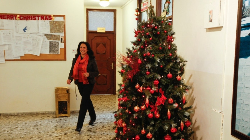 "In this photo taken on Monday, Dec 17, 2012, Bethlehem's first female mayor, Vera Baboun, walks out of her office in the West bank city of Bethlehem. Bethlehem's first female mayor, Vera Baboun, can't walk through the main square of the biblical town without being stopped by admirers.""This is our new mayor, who is turning Bethlehem into one of the greatest cities in the world,"" a tour guide hollered to a group of Christian tourists passing by the Church of the Nativity, built over the grotto where tradition says Jesus was born. After seven years of Islamist Hamas control of Bethlehem that drained the town of international aid funds, Baboun, a Christian, and her colleagues from the more moderate Fatah Party hope to turn things around, starting with the Christmas season. (AP Photo/Majdi Mohammed)"