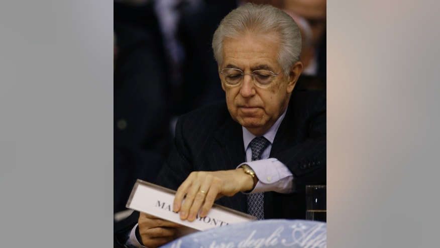 Italian Premier Mario Monti moves his tag name as he delivers his speech at the Foreign Ministry for the Italian Ambassadors conference in Rome, Friday, Dec. 21, 2012. Monti pledged to resign as soon as the budget law is passed after Silvio Berlusconi yanked support for his government, accelerating national elections now expected in February. The budget law was approved Friday afternoon. (AP Photo/Gregorio Borgia)