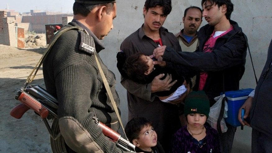 Dec. 21, 2012: A Pakistani health worker administers anti-polio drops to a child under security in Lahore, Pakistan.