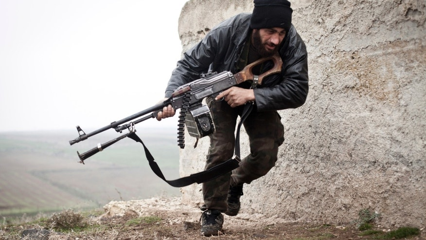 Dec. 17, 2012: In this photo, a Free Syrian Army fighter takes cover during fighting with the Syrian Army in Azaz, Syria.