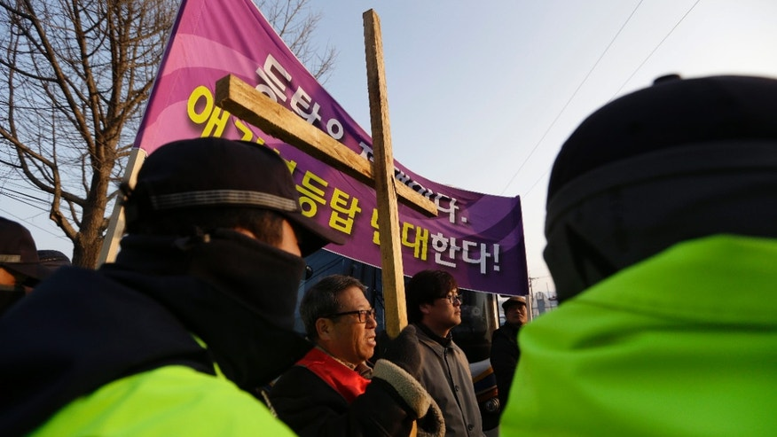 "Local residents are blocked by police officers as they try to block Christian groups who light a 30-meter-tall (100-foot-tall) steel Christmas tree with about 30,000 light bulbs that would be visible by North Koreans living near the Demilitarized Zone dividing the two Koreas, near the western mountain peak known as Aegibong in Gimpo, South Korea, Saturday, Dec. 22, 2012. The letters read ""Oppose, the light bulbs at Aegibong."" (AP Photo/Lee Jin-man)"