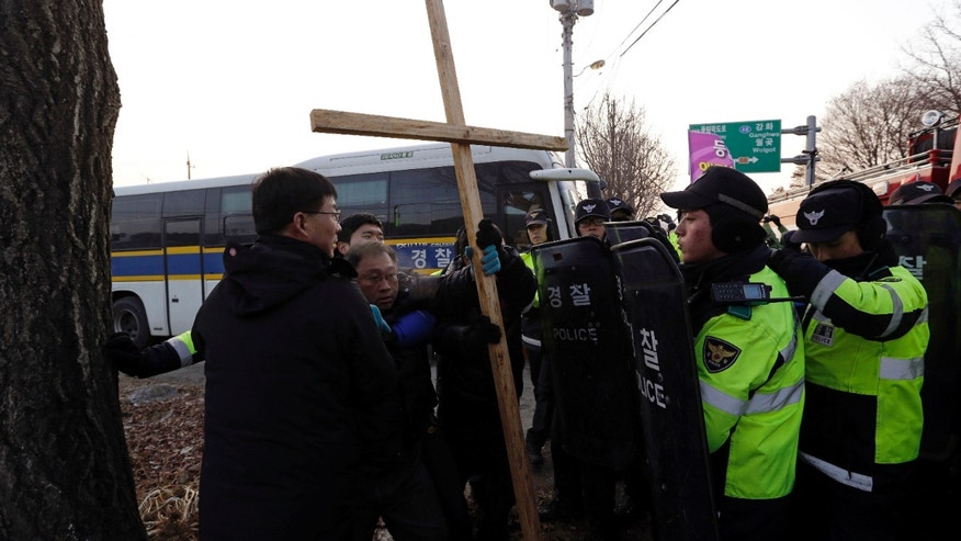 Local residents, second from left, is blocked by police officers as he tries to block Christian groups which light a 30-meter-tall (100-foot-tall) steel Christmas tree with about 30,000 light bulbs that would be visible by North Koreans living near the Demilitarized Zone dividing the two Koreas, near the western mountain peak known as Aegibong in Gimpo, South Korea, Saturday, Dec. 22, 2012. (AP Photo/Lee Jin-man)