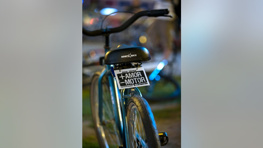 "In this Nov. 28, 2012 photo, a sign decorates a bicycle that reads in Spanish ""More love, less motor"" in Buenos Aires, Argentina. Civic leaders have tried to make Buenos Aires a bicycle-friendly city, but that's been stymied by another government initiative, protectionist import bans designed to spur domestic production that have instead strangled supplies of everything from bananas to prescription drugs. For cyclists, fewer bikes are available because the business has mostly relied on foreign-made parts. (AP Photo/Natacha Pisarenko)"