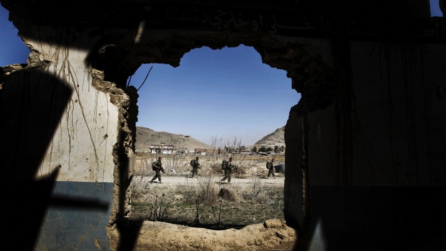 FILE - In this March 22, 2011, file photo, Afghan National Special Force soldiers patrol during a training session, seen through a destroyed building at Camp Morehead on the outskirts of Kabul, Afghanistan. U.S. soldiers serving in one of southern Afghanistan's most violent areas say they are successfully training the Afghans to secure their country and their progress so far will play a large role in determining how many more American troops President Barack Obama sends home next year. (AP Photo/Dar Yasin, File)