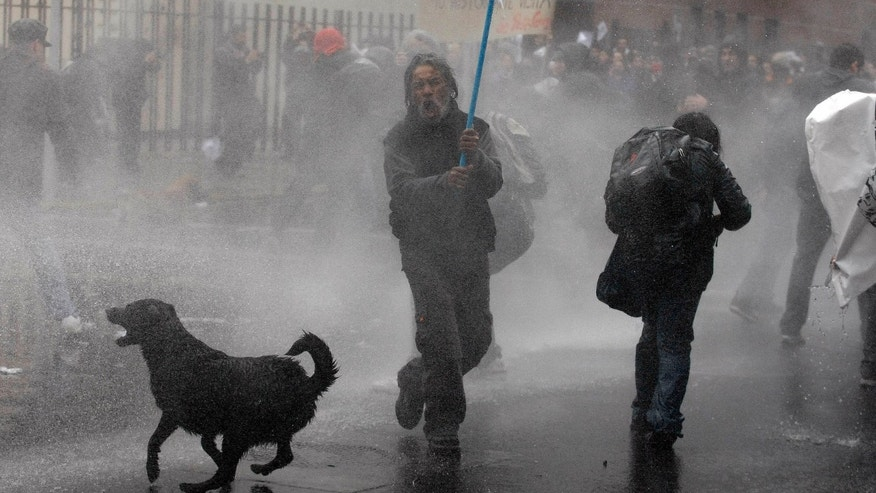 FILE - In this June 10, 2012 file photo, a dog runs in the spray as riot police use water cannons against demonstrators during a protest against the premiere of a documentary about the late Gen. Augusto Pinochet in Santiago, Chile. As the protests become fixtures in this modernizing capital, normally unnoticed street dogs have become stars in their own right. (AP Photo/Luis Hidalgo, File)