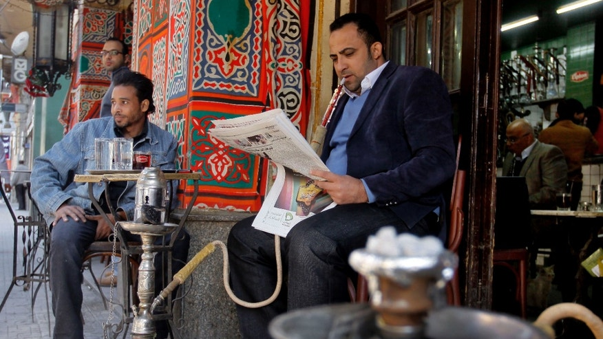 "An Egyptian man reads a newspaper at a coffee shop in Cairo, Egypt, Sunday, Dec. 23, 2012. Egypt's opposition called Sunday for an investigation into allegations of vote fraud in the referendum on a deeply divisive Islamist-backed constitution after the Muslim Brotherhood, the main group backing the charter, claimed it passed with a 64 percent ""yes"" vote. Official results have not been released yet and are expected on Monday. (AP Photo/Amr Nabil)"