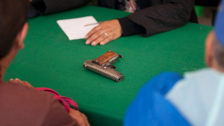"A gun sits on a table as it is turned over to a city employee, top, by a civilian, bottom, as part of a government program in which the government exchanges people's guns for bicycles, computers, tablets or money, on Christmas Eve in the Iztapalapa neighborhood of Mexico City, Monday, Dec. 24, 2012. Mexico City is sponsoring a program offering cash, toys and computer gear in exchange for guns in the rough neighborhood after a 10-year-old boy was killed by a stray bullet as he sat inside a movie theater. In November, 10-year-old Hendrik Cuacuas was hit in the head by a 9-mm bullet during the Disney film ""Wreck-It Ralph."" (AP Photo/Alexandre Meneghini)"