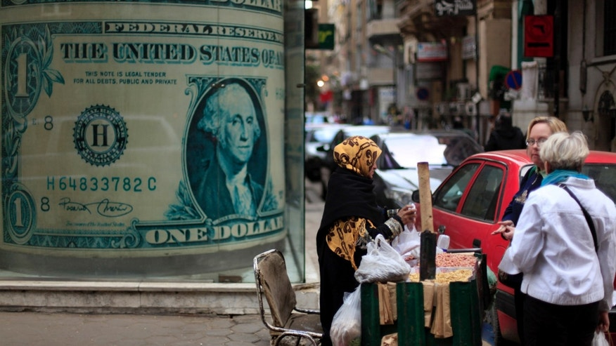 Dec. 25, 2012 - An Egyptian vendor sells nuts in front of a giant poster of a U.S. dollar outside a currency exchange office in Cairo.