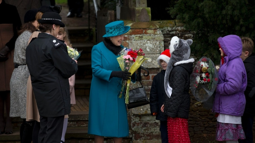 Dec. 25, 2012 - Britain's Queen Elizabeth II smiles as she receives flowers from children after attending the traditional Christmas Day church service in Sandringham, England.