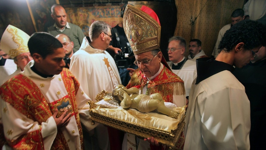 Latin Patriarch of Jerusalem Fouad Twal, center, holds the Baby Jesus as he and clergy arrive to pray at the Grotto, traditionally believed by Christians to be the birthplace of Jesus Christ, at the Church of the Nativity, in the West Bank town of Bethlehem, early Tuesday, Dec. 25, 2012. (AP Photo/Abed Al Hashlamoun, Pool)