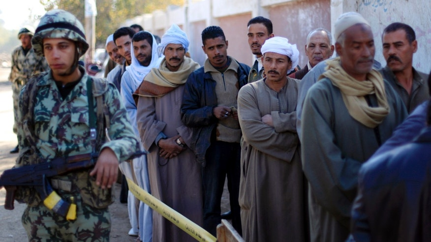 FILE - In this Saturday, Dec. 22, 2012 file photo, Egyptians line up outside a polling station wait their turn to cast their votes during the second round of a referendum on a disputed constitution drafted by Islamist supporters of President Mohammed Morsi in Fayoum, about 100 kilometers (62 miles) south of Cairo, Egypt. When election-time rolls around, this impoverished rural province has proven one of Egypt's most die-hard bastions of support for Islamists, handing them lopsided victories. The referendum that approved Egypt's Islamist-backed constitution was no exception, with nearly 90 percent of voters here supporting the charter. But even here, voices of discontent with the Muslim Brotherhood are emerging, something the liberal and secular opposition is hoping to build on in upcoming parliament elections.(AP Photo/Khalil Hamra, File)