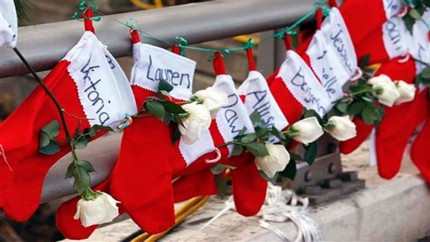Christmas stockings with the names of shooting victims hang from railing near a makeshift memorial near the town Christmas tree in the Sandy Hook village of Newtown, Conn.
