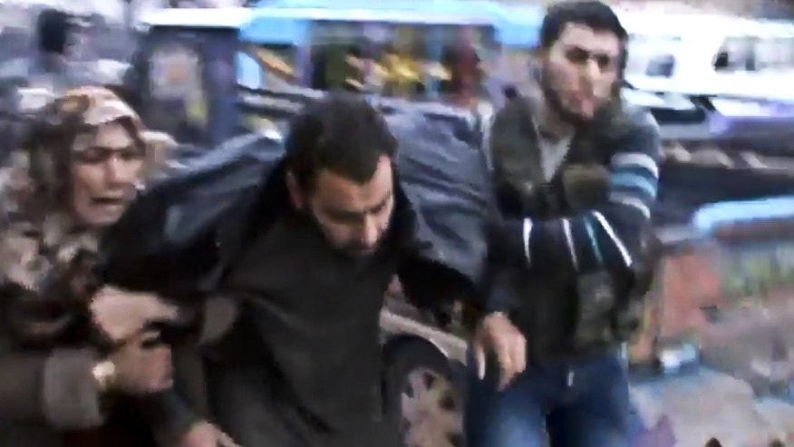 Dec. 23, 2012 - Image taken from video (obtained from Shaam News Network) shows Syrians helping a wounded man after a government airstrike hit the Hama Suburb of Halfaya, Syria.
