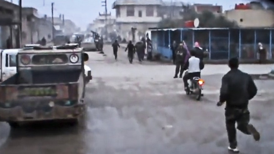 Dec. 23, 2012 -  Image taken from video (obtained from the Shaam News Network) shows Free Syrian Army fighters running towards the scene after a government airstrike hit Hama Suburb of Halfaya, Syria.