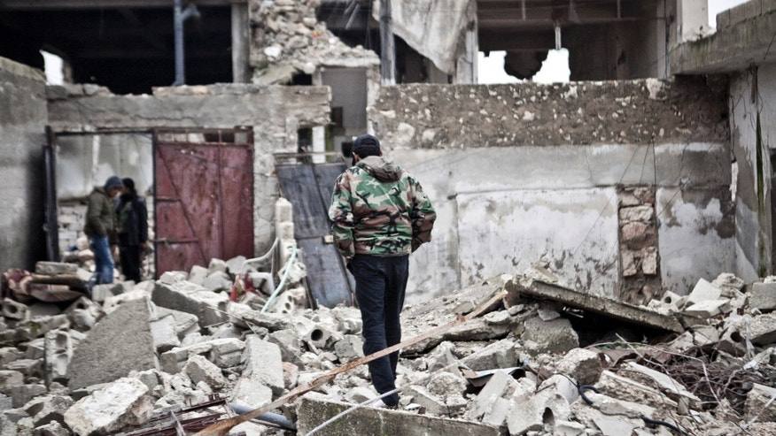 Dec. 22, 2012 - Free Syrian Army fighters walk amid the ruins of a village situated a short distance from an area where fighting between rebels and government forces continues.