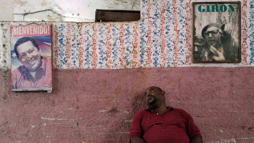 FILE - In this Dec. 10, 2012 file photo, a worker who sells vegetables takes a rest against a wall featuring posters of Venezuela's President Hugo Chavez, left, and former Cuban leader Fidel Castro, in Havana, Cuba.  Cuba's state TV cut from a nightly soap opera to the televised speech on Dec. 8, 2012, where Chavez revealed that his cancer had returned for a second time; facing his fourth cancer surgery in 18 months. The news shocked not only Venezuelans but millions of Cubans who have come to depend on Chavez's largesse for everything from subsidized oil to cheap loans. (AP Photo/Franklin Reyes, File)