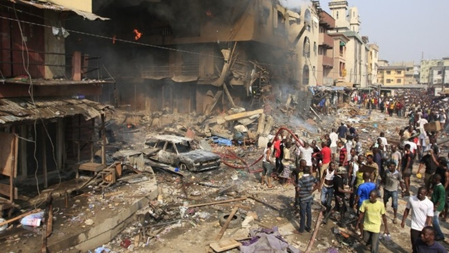 Dec. 26, 2012: People gather at the site of a fire on Lagos Island in Lagos, Nigeria. An explosion ripped through a warehouse Wednesday where witnesses say fireworks were  stored in Nigeria's largest city, sparking a fire.