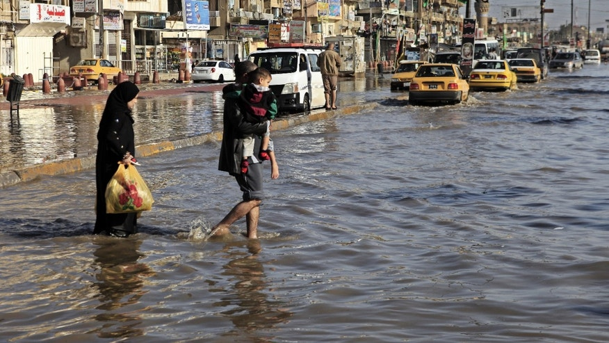 An Iraqi family make their way through flood water,  after heavy rain fell in Baghdad, Iraq, Wednesday, Dec. 26, 2012. (AP Photo/Karim Kadim)