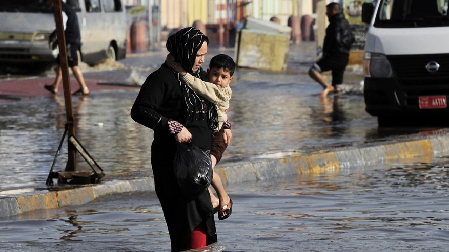 An Iraqi woman carries her child as wades through flood water,  after heavy rain fell in Baghdad, Iraq, Wednesday, Dec. 26, 2012. (AP Photo/Karim Kadim)