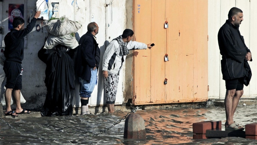 Iraqis make their way through flooded streets after heavy rain fell in Baghdad, Iraq, Wednesday, Dec. 26, 2012. (AP Photo/Karim Kadim)