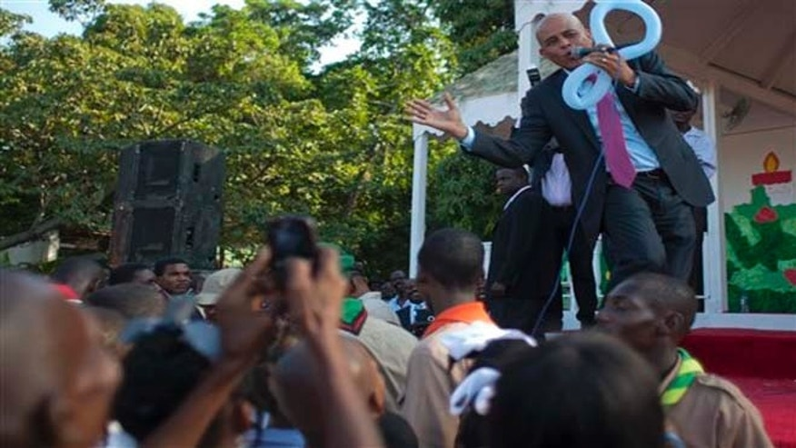 Haiti's President Michel Martelly, top, sings while dancing during a Christmas gift distribution event at the national palace in Port-au-Prince, Haiti, Wednesday Dec. 19, 2012.