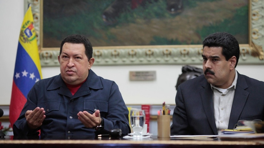 FILE - In this Dec. 8, 2012 file photo released by Miraflores Press Office, Venezuela's President Hugo Chavez, left, speaks beside his Vice President Nicolas Maduro during a televised speech form his office at the Miraflores presidential palace in Caracas, Venezuela. Cuba's state TV cut from a nightly soap opera to the televised speech, where Chavez revealed that his cancer had returned for a second time. Facing his fourth cancer surgery in 18 months, he named Maduro as his possible successor. (AP Photo/Miraflores Press Office, Marcelo Garcia, File)