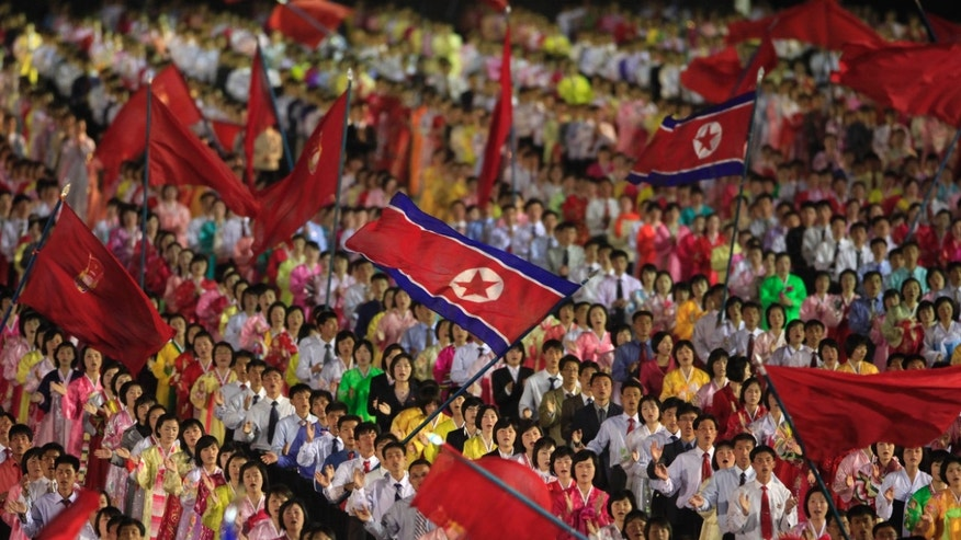 In this Monday, April 16, 2012 photo, students wave the national flags at an evening dancing party and performance at Kim Il Sung Square to commemorate late President Kim Il Sung's 100th birthday in Pyongyang, North Korea. (AP Photo/Ng Han Guan)
