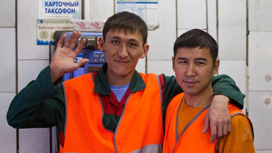 In this Aug. 27, 2012, photo, Uzbekistan natives and subway janitors Kushan, right, and Umid pose for a photo in Moscow. The old Moscow is rapidly giving way to a multi-ethnic city where Muslims from Central Asia are the fastest growing sector of the population. (AP Photo/Misha Japaridze)