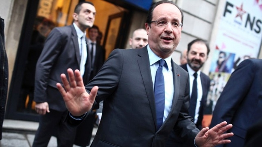Dec. 21, 2012: France's President Francois Hollande, center, gestures as he leaves the Europe 1 radio station after an interview, in Paris.
