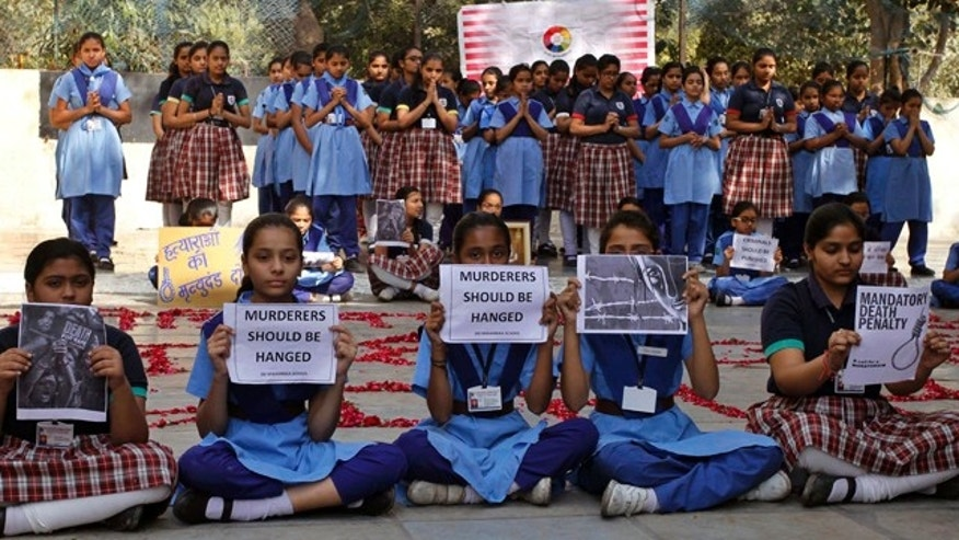 Dec. 29, 2012: Indian schoolgirls hold placards during a prayer ceremony to mourn the death of a 23-year-old gang rape victim, at a school in Ahmadabad, India.