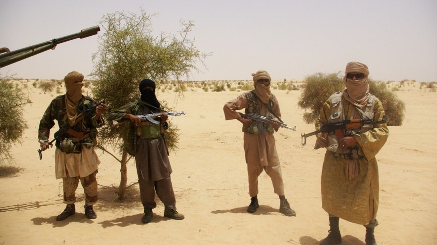 April 24, 2012: Fighters from Islamist group Ansar Dine stand guard during a hostage handover in the desert outside Timbuktu, Mali.